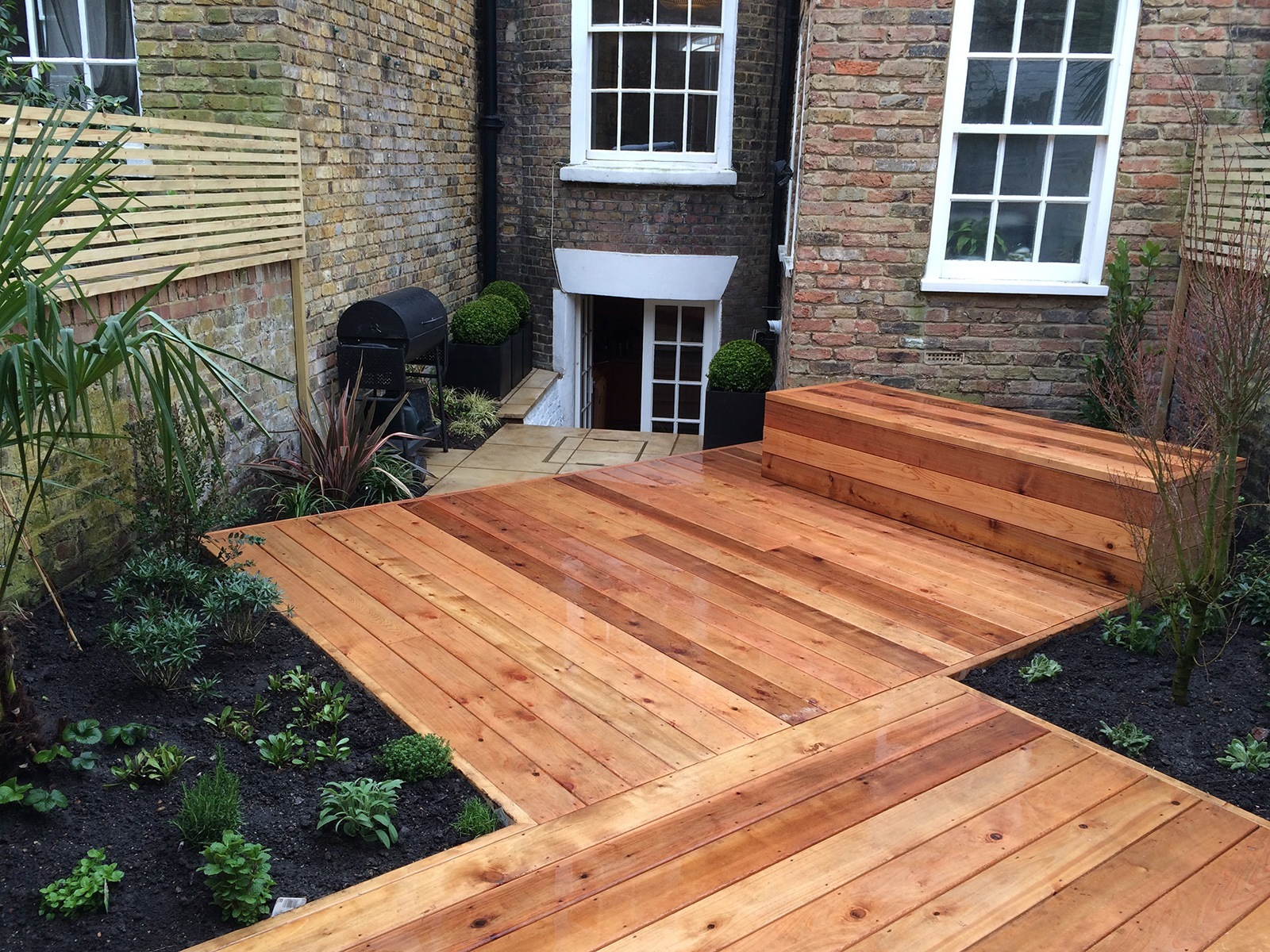 Decking set at an angle to the boundary walls breaks up this tight square garden and makes it feel bigger.