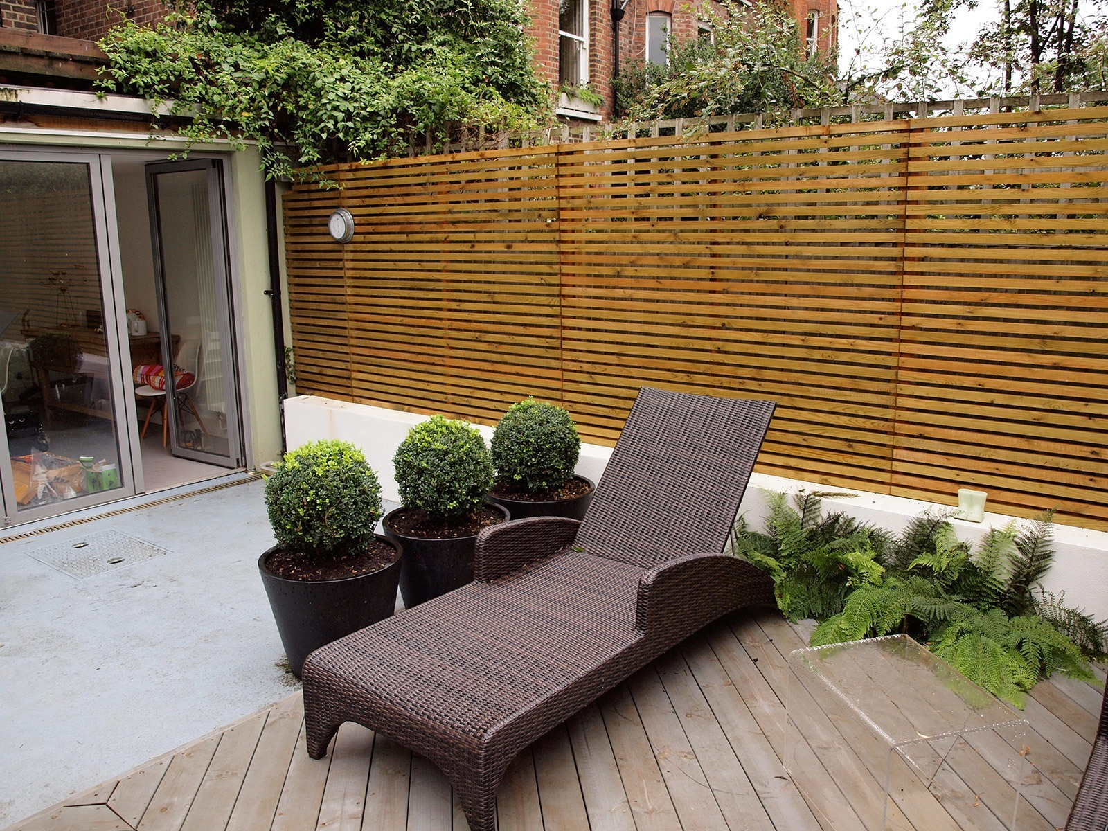 Modern garden furniture and planters and a very limited plant palette reinforce the sense of controlled neatness.