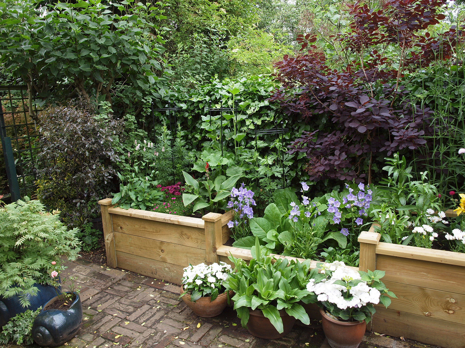 High quality raised planters are used in one section to give a change of level and increase the visual interest .